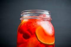 Röd coctail med körsbäret och limefrukt i krus på den lantliga bakgrunden royaltyfri bild