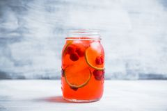 Röd coctail med körsbäret och limefrukt i krus på den lantliga bakgrunden arkivfoton