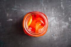 Röd coctail med körsbäret och limefrukt i krus på den lantliga bakgrunden royaltyfri fotografi