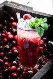 Röd coctail med is, mintkaramellen och körsbäret på en bärbakgrund arkivbild
