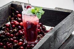 Röd coctail med is, mintkaramellen och körsbäret på en bärbakgrund royaltyfria foton
