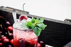 Röd coctail med is, mintkaramellen och körsbäret på en bärbakgrund royaltyfri fotografi