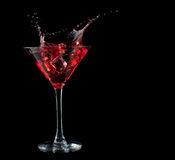 Röd coctail som plaskar in i exponeringsglas på svart Arkivfoto