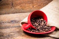 Röd coffeecup och platta med spillda coffeebeans Arkivfoto