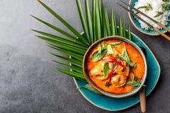 RÖD CURRY FÖR THAILÄNDSKA RÄKOR Soppa för curry Thailand för thailändsk tradition mjölkar röd med räkaräkor och kokosnöten Panaen royaltyfri bild