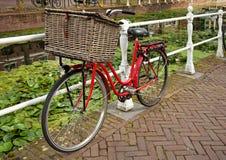 Röd cykel bredvid en kanal i Nederländerna Arkivbild