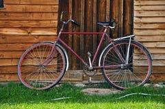 Röd cykel för tappning nära ett trähus Arkivbild