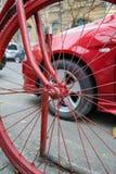 Röd cykel och röd bil arkivbilder
