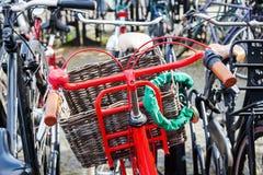 Röd cykel på en cykelparkeringsplats Arkivbild