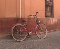 Röd cykel som vilar på väggen arkivbild