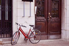 Röd cykelbenägenhet mot en byggnad Royaltyfri Foto