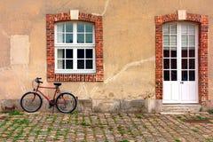 Röd cykelbenägenhet mot en gammal lantbrukarhemvägg royaltyfri fotografi