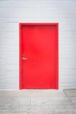 Röd dörr i den vita tegelstenväggen Arkivbild