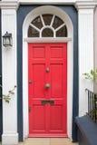 Röd dörr i det typiska London huset Arkivbild