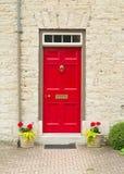 Röd dörr och blommor Arkivbilder