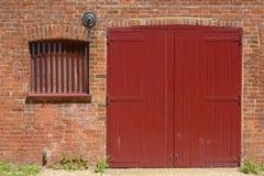 Röd dörr och fönster i tegelstenvägg Royaltyfri Fotografi