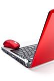 Röd datormus och röd anteckningsbok Arkivbilder