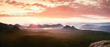 Röd dimmig landskappanorama i berg Fantastisk drömlik soluppgång på steniga berg Dimmig dimmig dal under Royaltyfria Bilder