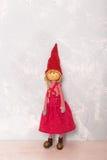 Röd dockaflicka för leksak på trägolvet Arkivfoto