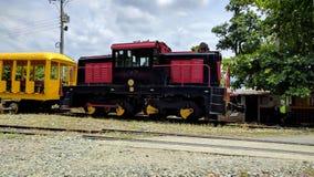 Röd drevmotor som bogserar en gul drevbil royaltyfri foto