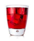 Röd drink med iskuber i ett exponeringsglas royaltyfria bilder