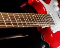 Röd elektrisk gitarr på svart bakgrund Fotografering för Bildbyråer