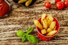 Röd emaljerad kopp med potatissmåfiskar som tjänas som med tomatsås och gravade gurkor i keramiska krukor som dekoreras med basil Royaltyfria Bilder