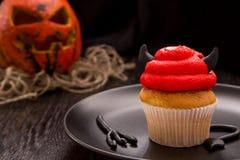 Röd en muffin för allhelgonaafton i formen av jäkeln Arkivfoto