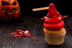 Röd en muffin för allhelgonaafton med yxa Royaltyfria Foton