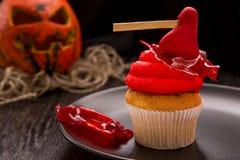 Röd en muffin för allhelgonaafton med yxa på den svarta plattan Arkivbild