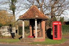 Röd engelsk telefonask & krigminnesmärke Arkivfoto