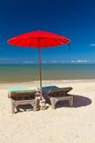 Röd ett slags solskydd med deckchair på tropisk strand Fotografering för Bildbyråer