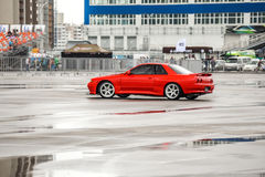 Röd färg för Nissan horisont R 32 på en våt väg fotografering för bildbyråer