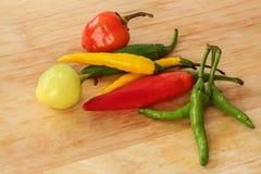 Röd färgrik chili -, göra grön, gulna - wood bakgrund Royaltyfria Foton