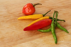 Röd färgrik chili -, göra grön, gulna - wood bakgrund Arkivbild