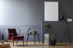 Röd fåtölj bredvid tabellen i grå lägenhetinre med mocku royaltyfria bilder