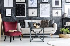 Röd fåtölj nära den beigea soffan i modern vardagsruminre med royaltyfri fotografi