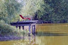 Röd fåtölj på en träbro med metspön över vattnet royaltyfri bild
