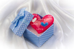 Röd förälskelsehjärta i lite blå gåvaask Fotografering för Bildbyråer
