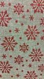 Röd ferie blänker snöflingor på naturlig säckvävtextur Royaltyfri Bild