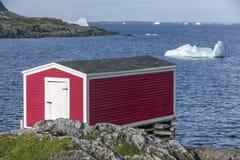 Röd fiskeetapp på kusten, isberg i fjärden, Newfoundland royaltyfri bild