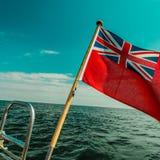 Röd flagga för UK den brittiska maritima flaggan som flygas från yachten Royaltyfri Bild