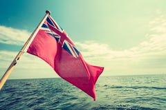 Röd flagga för UK den brittiska maritima flaggan som flygas från yachten Arkivfoton