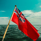 Röd flagga för UK den brittiska maritima flaggan som flygas från yachten Arkivfoto