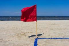 Röd flagga i vinden på den sandiga stranden Arkivfoton