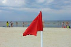 Röd flagga på en sandig strand Arkivbilder