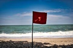 Röd flagga på en strand royaltyfri fotografi