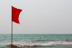 Röd flagga på havkusten som markerar det omvända flödet Arambol arkivbilder