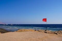 Röd flagga på kusten Arkivbild