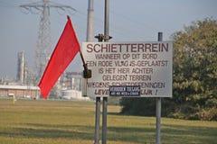 Röd flagga på schooting område med varningar för fara Detta skjuta område för lerduveskytte på maasvlaktehamnen i Rotterdam royaltyfri bild